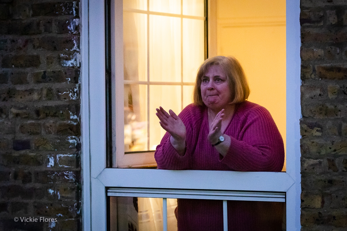 A Wapping resident pays her respects as she claps from her window on a Thursday evening