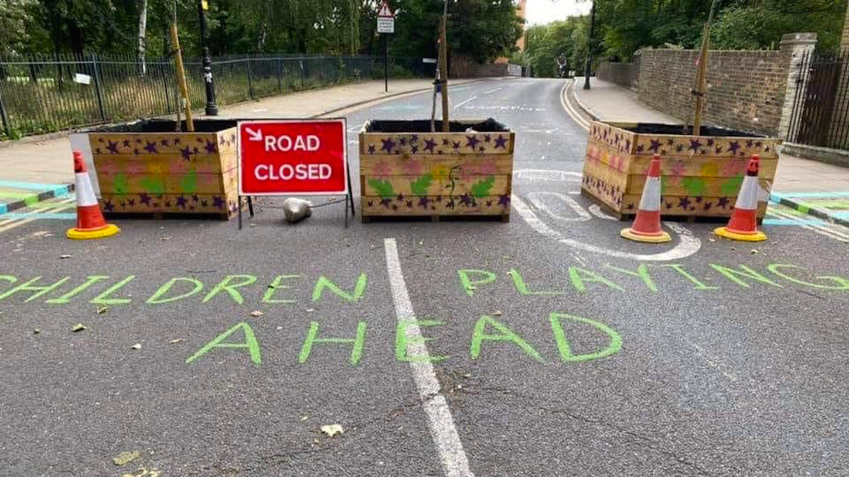 Photograph of Skew Bridge road blocks with 'children playing ahead' written in green chalk on road.