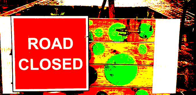 Road closed sign and planters in the Brick Lane rain